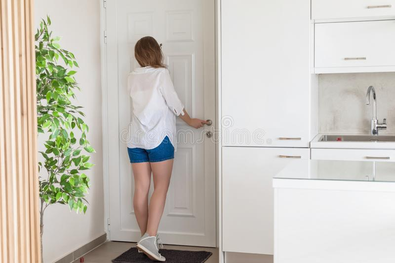 Woman in shirt and shorts looking in peephole door when somebody rings the doorbell.  royalty free stock photography