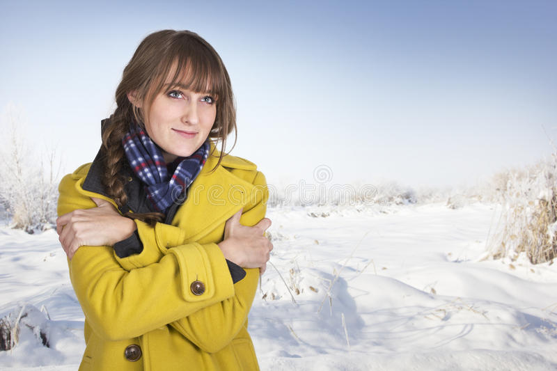 Woman Shivering on a cold winter day. A shivering, freezing cold woman in her yellow winter coat outdoors royalty free stock images