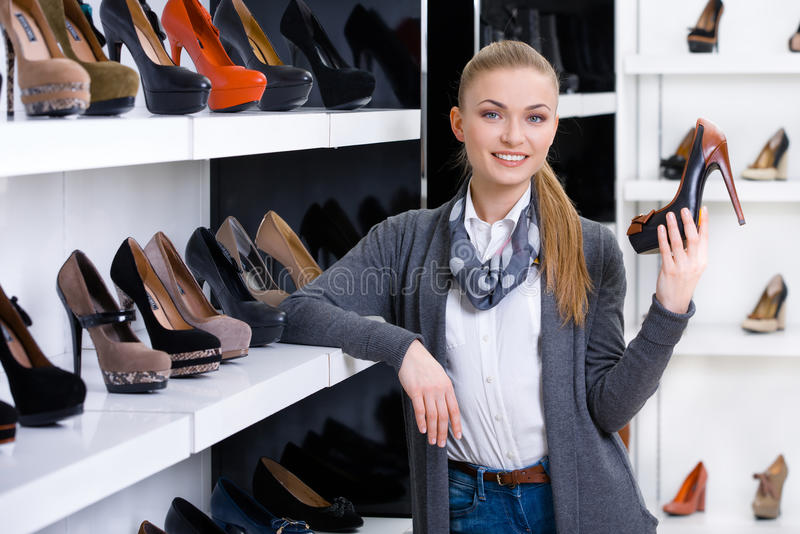 Woman with shoe in hand chooses stylish pumps stock image