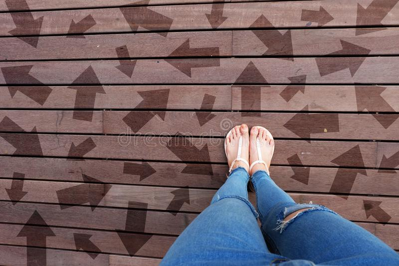 Woman Shoes with Drawn Direction Arrows Choices. Woman Feet and Sandal Standing on Wooden Floor Background stock image