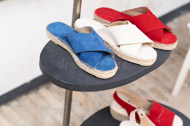 Woman shoes modern colorful french white red blue espadrilles for sale in shop street. A woman shoes modern colorful french white red blue espadrilles for sale royalty free stock images