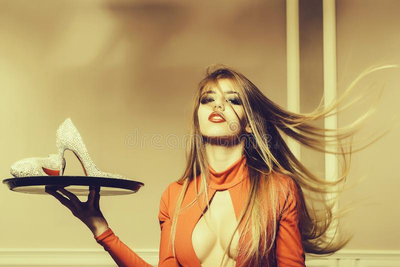 Woman with shoes on tray. Glamour sensual young woman with long windy hair straight body in orange dress with sparkling pair of elegant shoes on waiter tray stock images