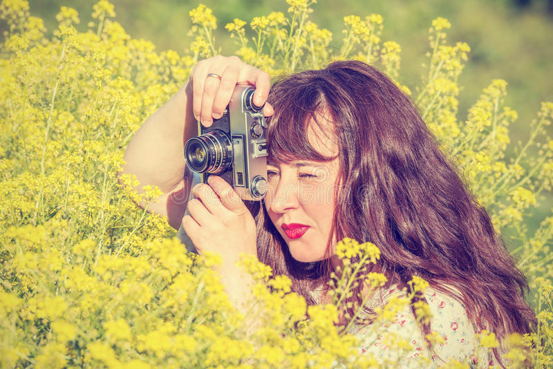 Woman shooting flowers on the meadow. stock image