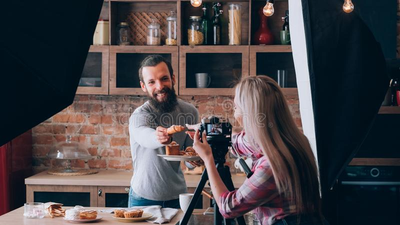 Shooting food blogger man backstage photography. Woman shooting food blogger. Photo session. Man at kitchen counter with plate of fresh pastries. Have a treat stock image