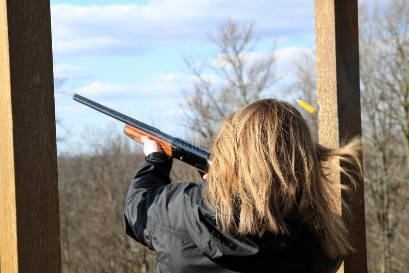 Woman shooting at trap shooting range. Young, blond, caucasian woman shoots her rifle with shell ejecting above head at a trap shooting range royalty free stock photos