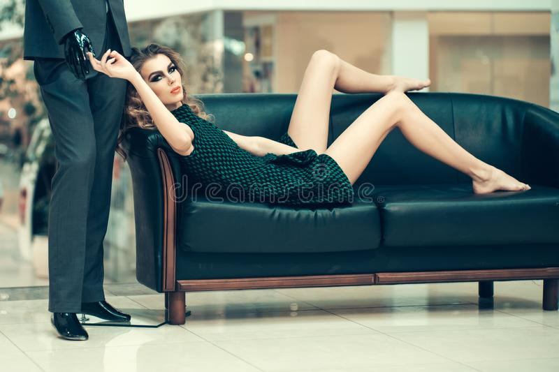 Woman shopper relax on sofa with fashion mannequin in shop. Girl shopaholic tired shopping. Shop, shopping, sale. Fashion, style, vogue. Beauty, look makeup royalty free stock images
