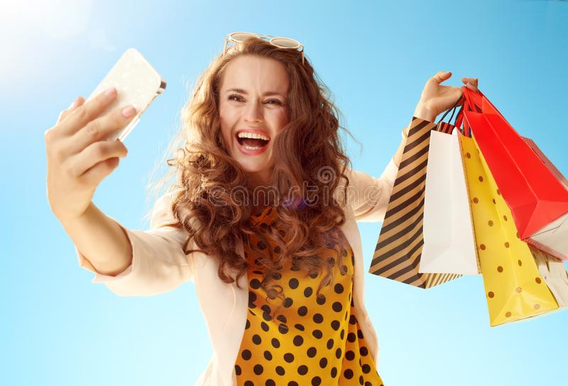 Woman shopper taking selfie with phone against blu. Smiling young woman in a light jacket with shopping bags taking selfie with smartphone against blue sky stock photos
