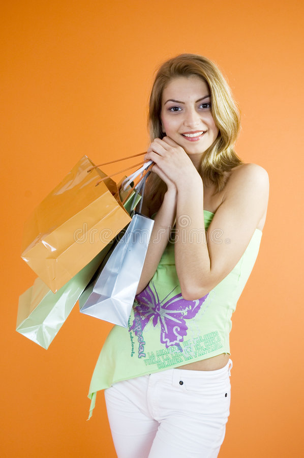 Woman Shopping. A happy Caucasian woman holding merchandise bags after a fun day of shopping royalty free stock image