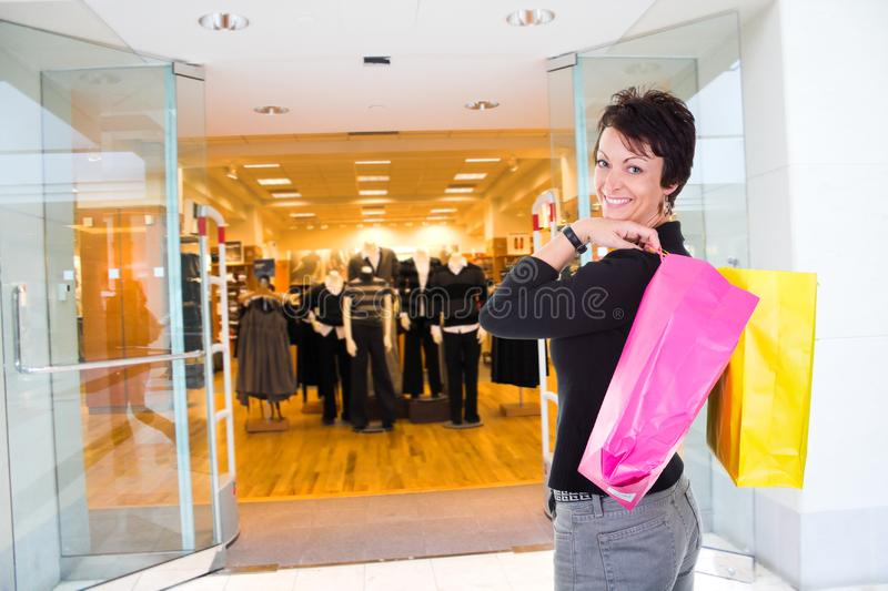Woman shopping. Happy woman holding bags shopping in mall stock image