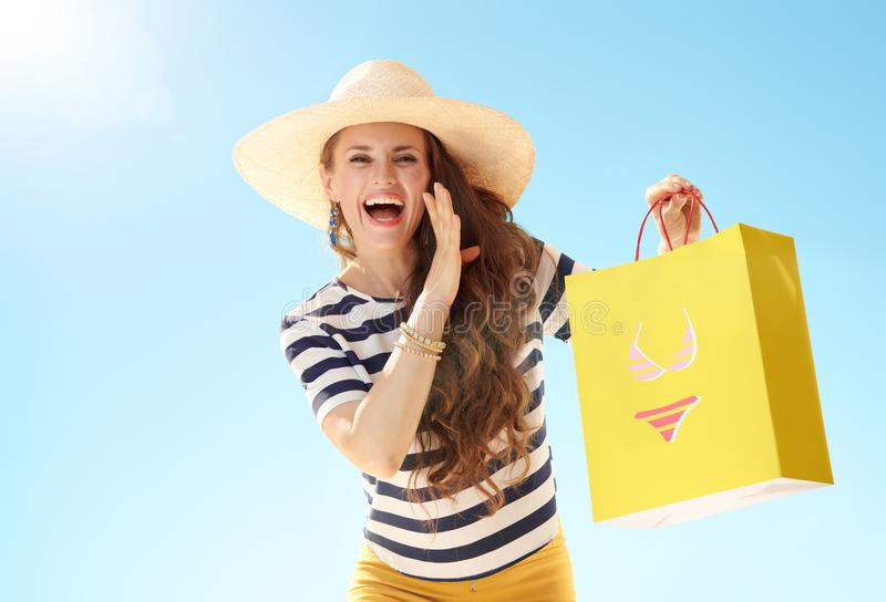 Woman with shopping bag with bikini telling exciting news royalty free stock images
