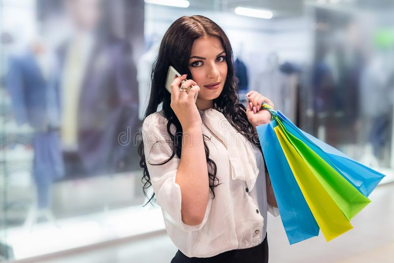 Woman with shopping bags calling to someone in mall stock photo