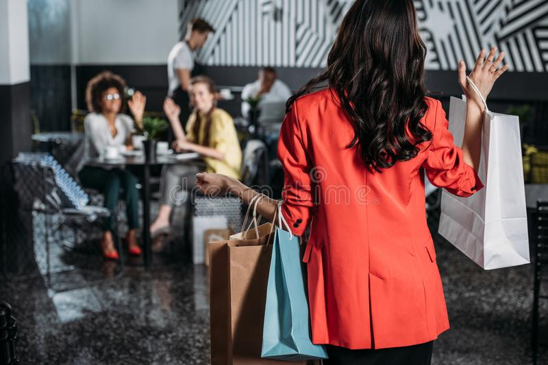 woman with shopping bags going to her friends stock photos
