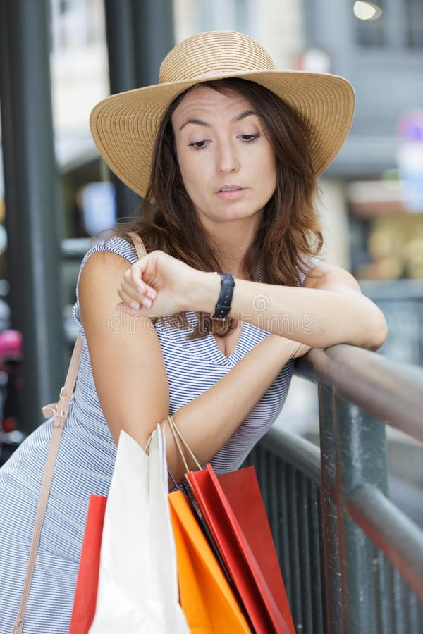 Woman with shopping bags looking at watch royalty free stock photography