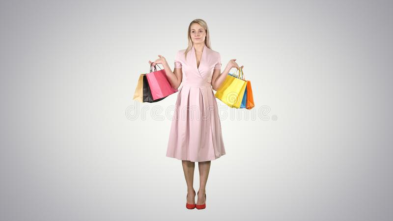 Woman with shopping bags in pink dress standing on gradient background. Full length portrait. Woman with shopping bags in pink dress standing on gradient stock images