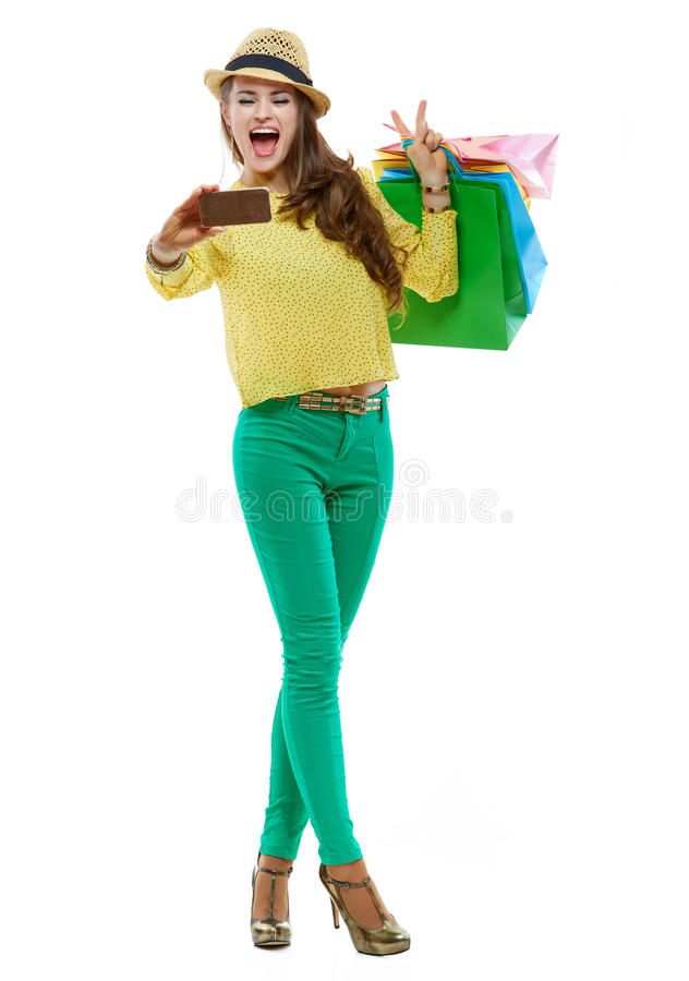 Woman with shopping bags showing victory and taking selfie. Colourful shopping vibes. Full length portrait of excited brunette woman in hat and bright clothes royalty free stock photos