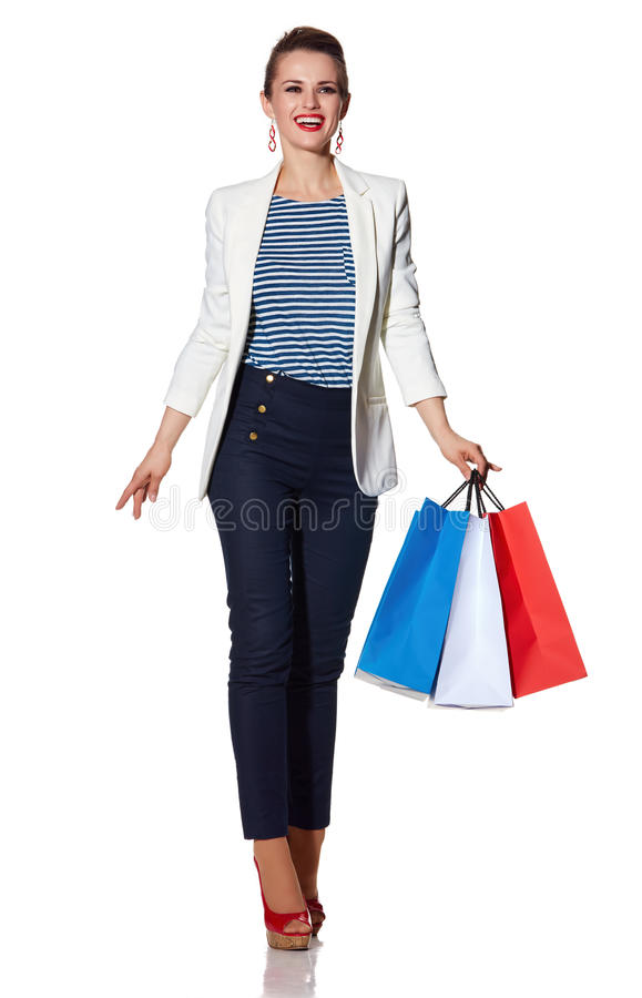 Woman with shopping bags on white background going forward. Shopping. The French way. Full length portrait of happy young woman with French flag colours shopping royalty free stock photography