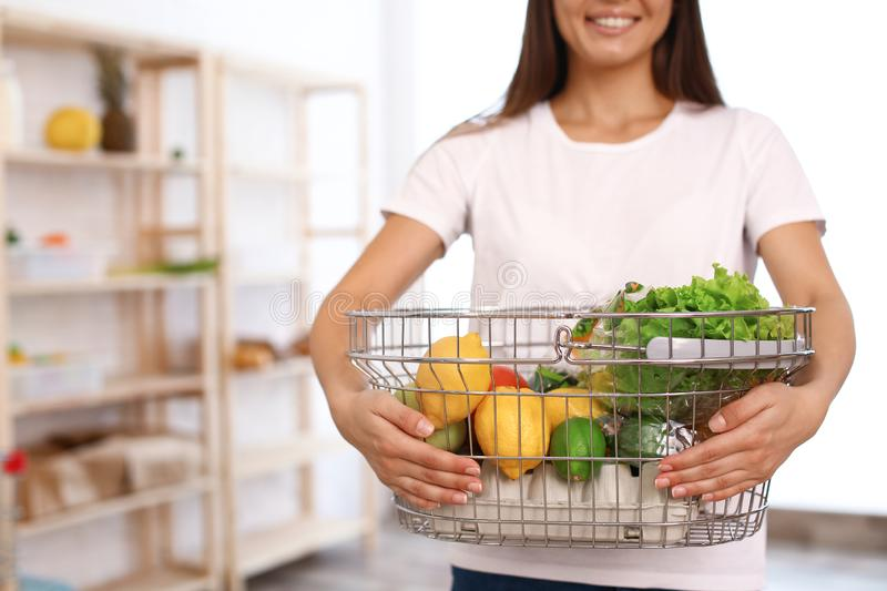 Woman with shopping basket full of products in grocery store. Closeup royalty free stock image