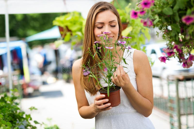 Happy woman shopping beautiful flowers in garden center royalty free stock photos