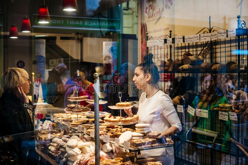 Woman shopping for bread bakery view from street stock photo