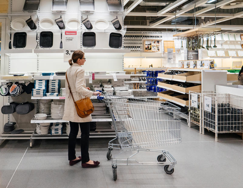 Woman with shopping cart inside IKEA decisions stock photography