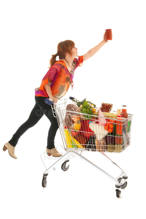 Woman with Shopping cart picking food from high cupboard. Woman with shopping cart full with dairy grocery products picking glass pot pasta sauce isolated over stock image