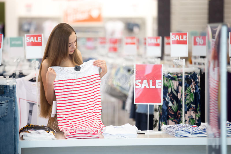 Woman in shopping centre choosing clothes. Beautiful young pretty woman in shopping centre store choosing clothes looking at trendy striped red and white dress royalty free stock image
