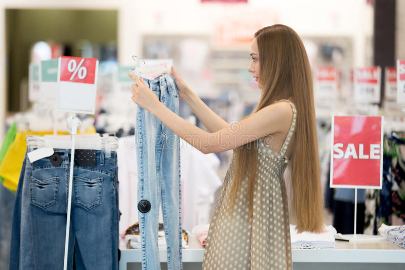 Woman in shopping centre choosing jeans. Profile portrait of long-haired young pretty woman in shopping centre store choosing clothes looking at jeans and royalty free stock photo