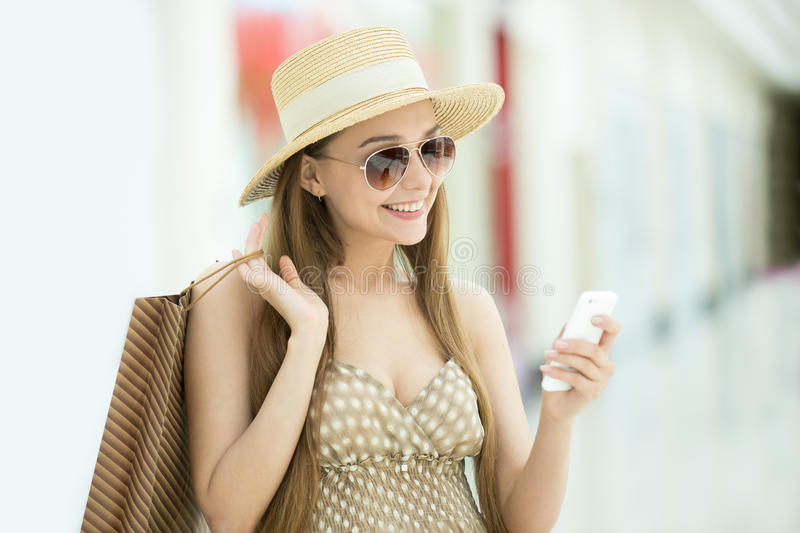 Woman in shopping centre looking at mobile phone. Portrait of young pretty happy smiling woman wearing hat and sunglasses standing in shopping center, holding royalty free stock image