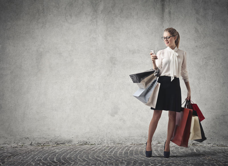 Woman shopping checking her phone stock images