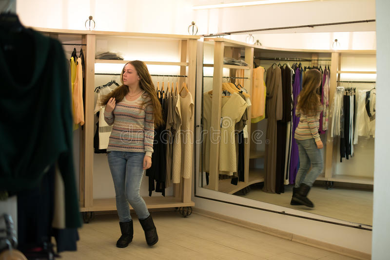 Woman shopping choosing dresses looking in mirror uncertain stock photos
