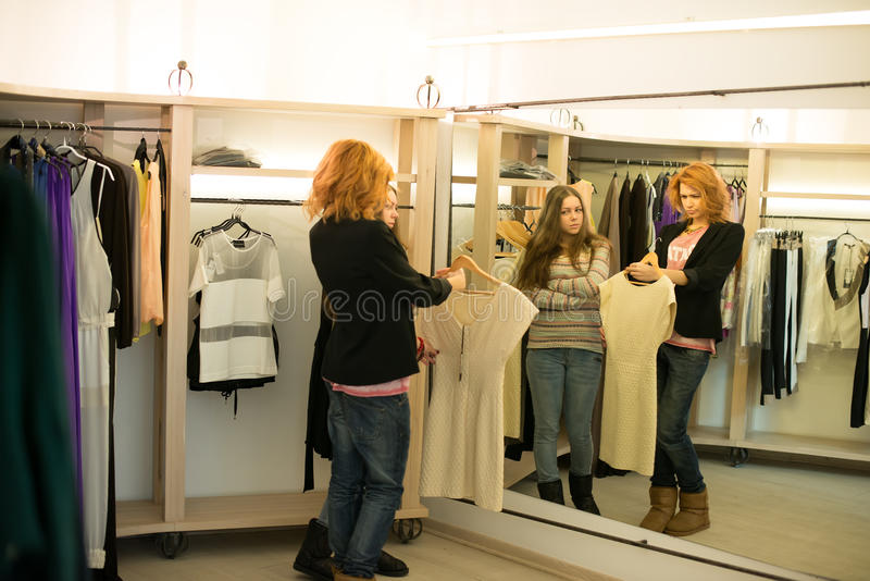 Woman shopping choosing dresses looking in mirror uncertain royalty free stock photo