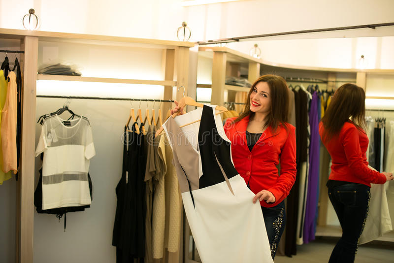 Woman shopping choosing dresses looking in mirror uncertain royalty free stock images