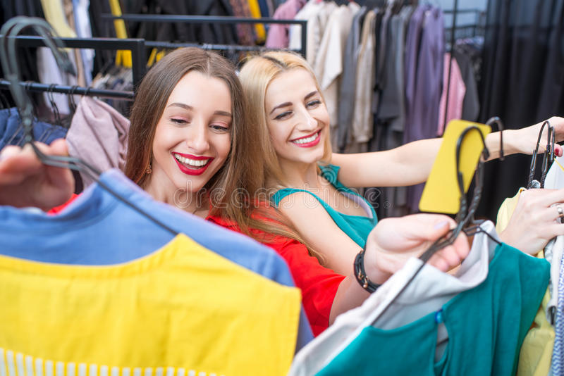 Woman shopping clothes. Beautiful women choosing garments in the clothing store. Female friends having fun shopping in the boutique royalty free stock images