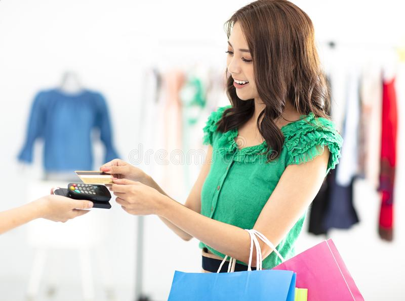 woman shopping in clothes store and paying by credit card stock image