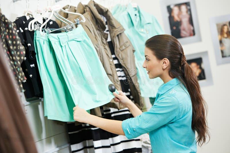 Woman shopping clothng. Woman choosing dress during shopping at garments apparel clothing shop stock photography
