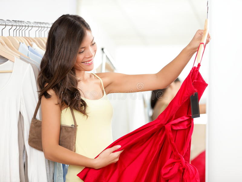 Woman shopping for dress. In clothing retail store. Beautiful multiracial Asian / Caucasian shopper girl choosing red dress in shop during sale royalty free stock images