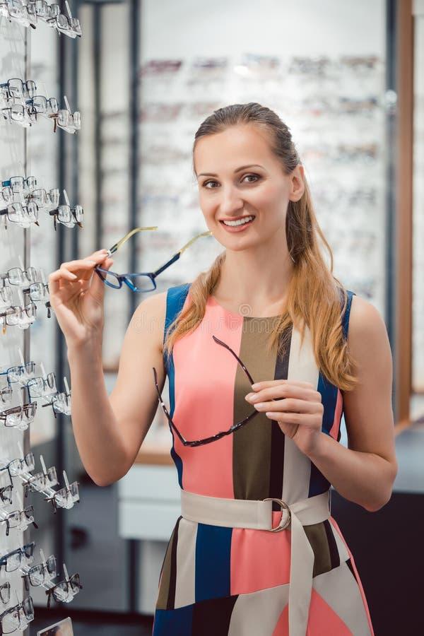 Woman shopping eyeglasses choosing between the models stock photography