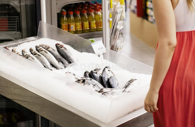 Woman shopping for fish in a supermarket royalty free stock images