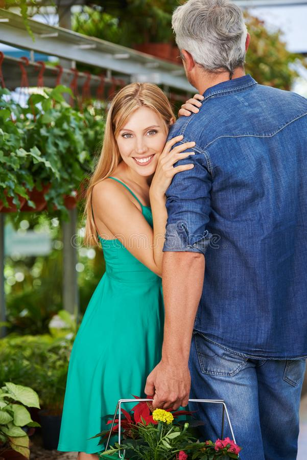 Woman is leaning against shoulder of man in garden center stock images
