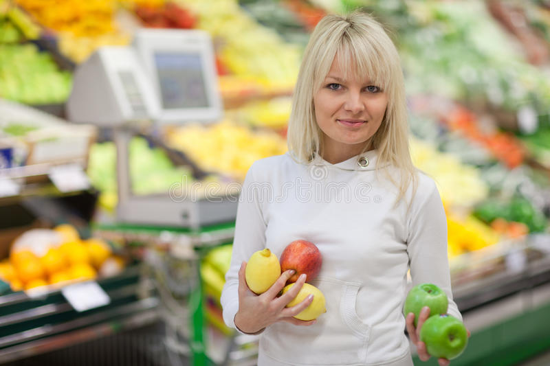 Woman shopping for fruits and vegetables. Beautiful young woman shopping for fruits and vegetables in produce department of a grocery store/supermarket stock photography