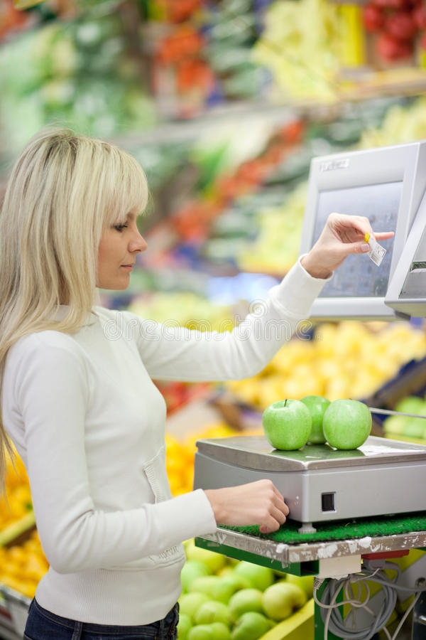 Woman shopping for fruits and vegetables. Beautiful young woman shopping for fruits and vegetables in produce department of a grocery store/supermarket royalty free stock photo