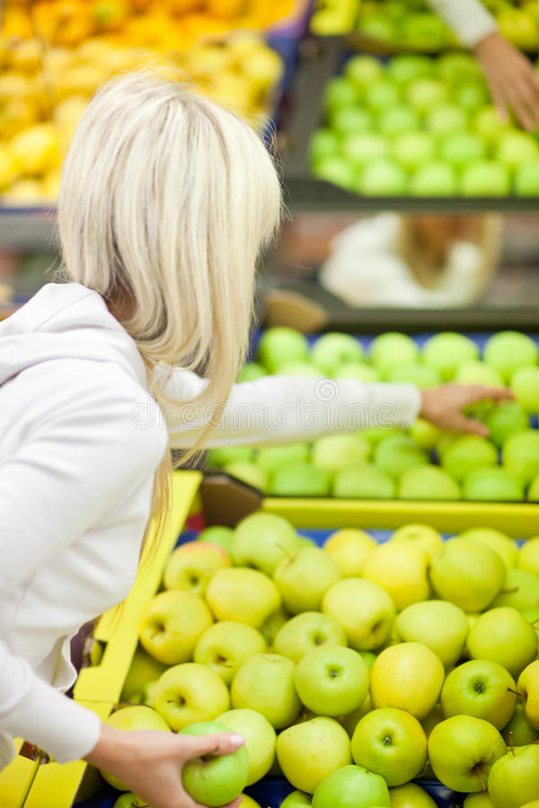 Woman shopping for fruits and vegetables. Beautiful young woman shopping for fruits and vegetables in produce department of a grocery store/supermarket royalty free stock images