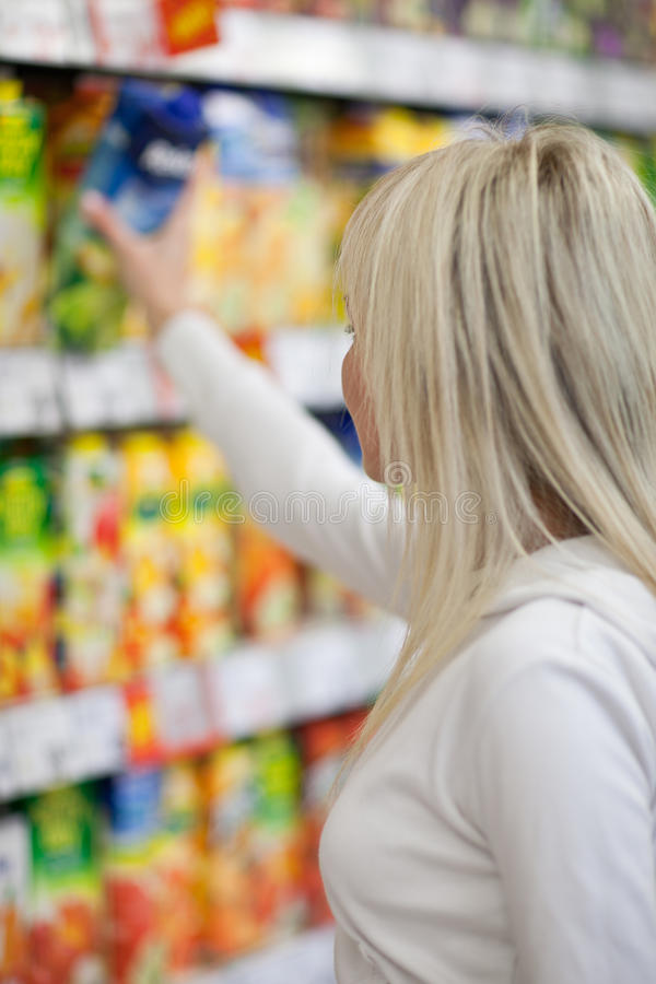 Woman shopping for fruits and vegetables. Beautiful young woman shopping for fruits and vegetables in produce department of a grocery store/supermarket royalty free stock photos