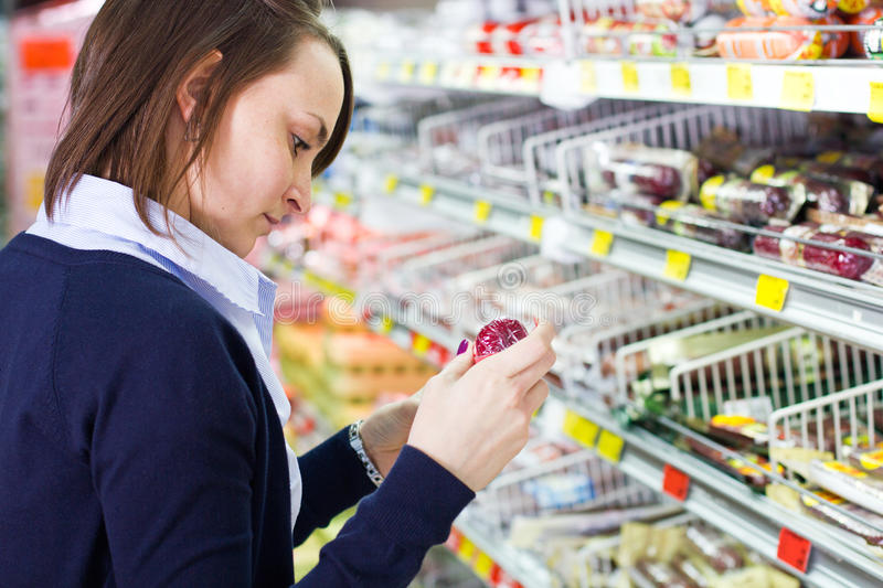 Woman shopping in grocery store. Young woman shopping in a grocery store looking at a product stock image