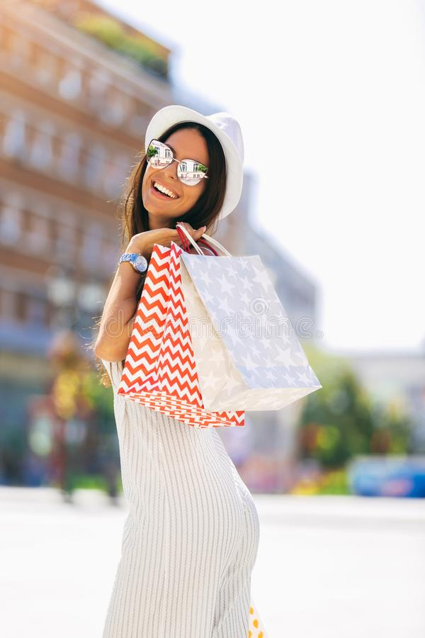 Woman in shopping. Happy woman with shopping bags enjoying in shopping stock photography