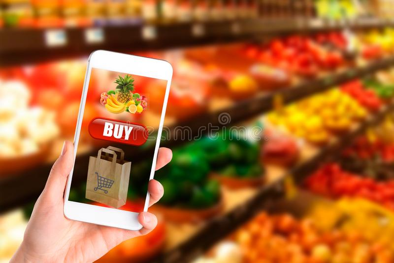 Woman shopping healthy food in supermarket background. Close up view girl buy products using digital gadget in store. Hipster at stock images