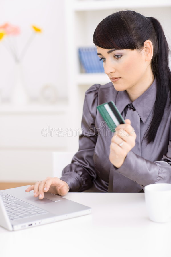 Woman shopping online. Young women shopping online at home, using laptop computer, holding credit card in hand stock image