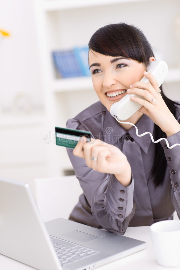 Woman shopping online. Smiling young women shopping online at home, holding credit card in hand and talking on phone stock photography