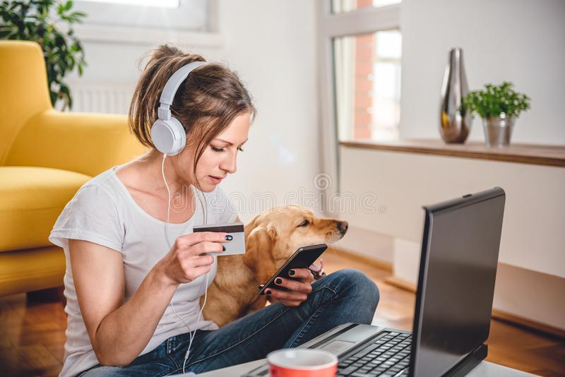 Woman shopping online and using credit card. Woman wearing white shirt and headphones shopping online on smart phone and using credit card stock photo