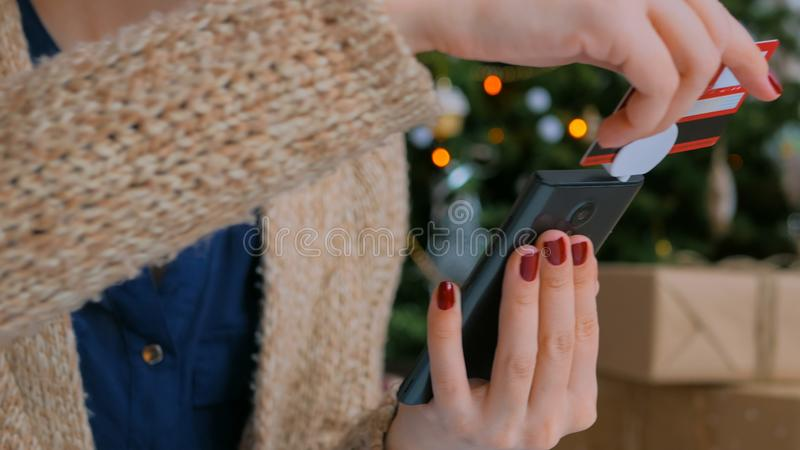 Woman shopping online and using smartphone with credit card reader device. Young woman buying goods from internet and using mobile credit card reader device with royalty free stock photography